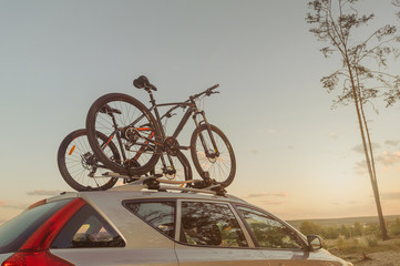 Car is transporting bicycle on the roof. Sunset.