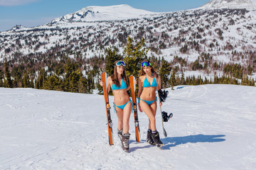 Two young women with ski and snowboard in blue swimsuits