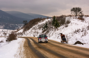 Volovets, Ukraine - December 16, 2016: traffic in mountainous rural area in winter. cart with one horse outscored by SUV on snowy countryside road