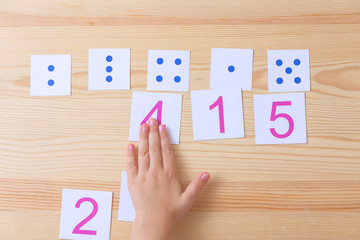 The child spreads cards with numbers to cards with dots. The study of numbers and mathematics