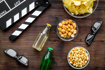 Crisp, popcorn, rusks and drink for watching film. Clapperboard and glasses on dark wooden background top view