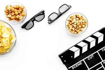 Fast food for watching film. Popcorn, rusks near glasses and clapperboard on white background top view