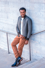 Winter Street Fashion in New York. African American guy wearing green coat, white knitting under sweater, brown pants, leather boot shoots, necklace, leaning against wall, looking away, smile..