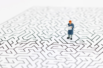 Miniature people: Businessman reading on center of maze. Concepts of finding a solution, problem solving and challenge.