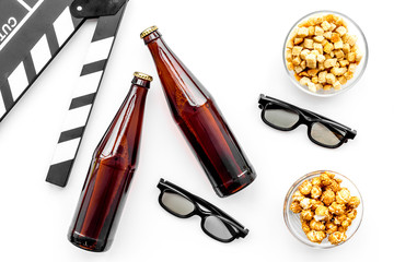 Popcorn, rusks for watching film. Clapperboard and glasses on white background top view