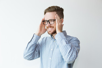 Photo sur Toile Portrait of Joyful Young Man In Glasses Touching Head