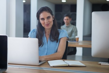 Smiling female executive working on laptop at desk