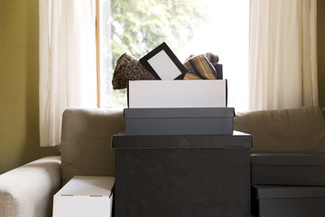 Move house concept. Carton boxes, shoe boxes and belongings on couch