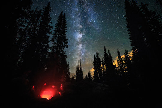 Family of four sitting around a campfire under stars and the milky way.