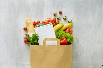 Paper bag of different health food and notebook white background