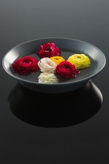 Red, white and yellow roses in glass bowl with water