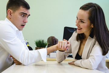 Young man and woman fight on his hands at the Desk in the office for a place Boss, head. The battle of the sexes, young couple having fun in the office.