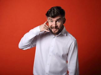 Smiling excited business man showing call me gesture on bright red background. Closeup portrait with empty copy space