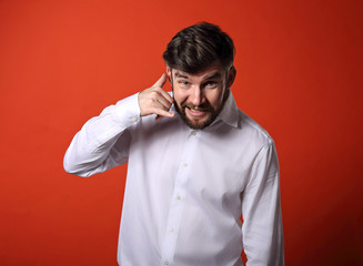 Smiling excited business man showing call me gesture with happy smiling on bright red background. Closeup portrait with empty copy space
