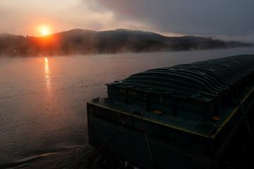 Fog rises at sunrise as tbe towboat MK McNally pushes barges on the Ohio River near Toronto