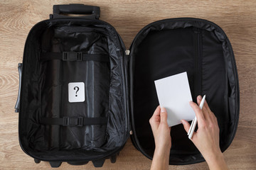 Opened empty, black travel bag with question mark on the wooden floor. Choice concept what kind of clothes, things and personal accessories to take on trip. Preparation for traveling.