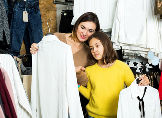 Mother and daughter examining various blouses