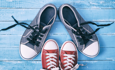 Two pairs of textile sneakers with loose laces stand opposite each other