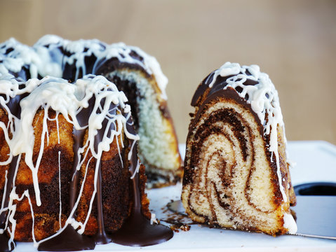 Marble bundt cake with dark and white chocolate icing sliced. Slice of marbled ring cake over cake server.