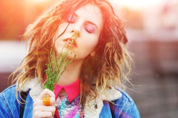 Young pretty girl with dreads with closed eyes and a tuft of grass in his hands outdoors on a bright day, close up
