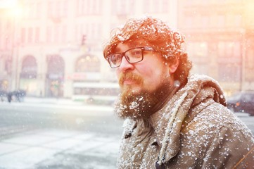 Reckless Russian bearded guy in glasses without a hat, covered with snow, walking in the center of St. Petersburg during a Blizzard on a cold winter day