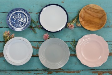 Empty plates with flower on wooden table