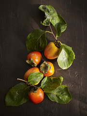 Still Life composition of persimmons with leaves