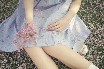 Young woman lying on the grass in bloom - Blossom prairie - Girl with a lilac flowers bouquet in the hands, detail of the knees - Resting on the grass - Alice in wonderland inspired