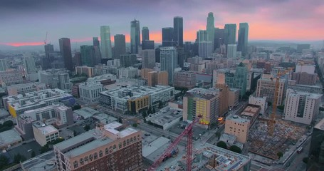 Klistermärke - Aerial pan across dramatic downtown Los Angeles skyline at sunset twilight dusk. 4K UHD