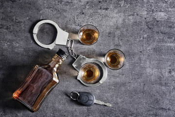 Composition with alcohol, handcuffs and car key on grey background. Don't drink and drive concept