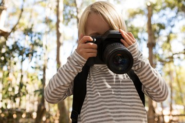 Little girl with a backpack holding dslr camera