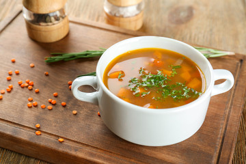 Dish with tasty lentil soup on wooden board