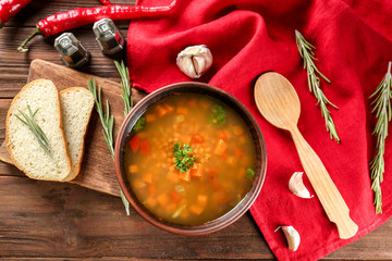 Dish with tasty lentil soup on table