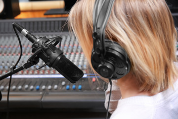 Female radio host broadcasting through microphone in studio