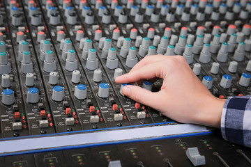 Radio host working with mixer in studio