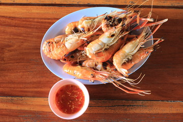 grilled shrimps in bowl on wooden table