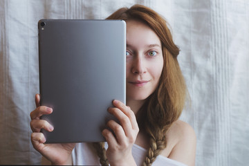 Beautiful ginger woman with metal tablet