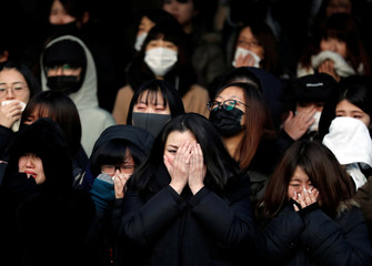 Fans of Kim Jong-hyun, lead singer of top South Korean boy band SHINee, react as a hearse carrying his coffin leaves during his funeral at a hospital in Seoul