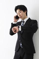 電話しながら時計を見る若いビジネスマン