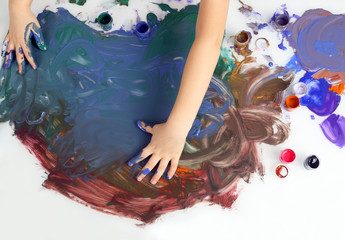 children's hands paint a picture with paints on white background.