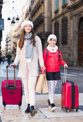 female and child girl going with baggage
