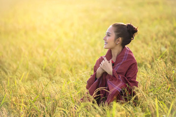 Asian girl standing and smiling in her rice field in the sun at dawn.