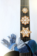 festive musical appetites/ biscuits in the form of snowflakes on the background of a guitar wrapped in scarf