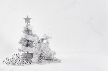 Christmas glitter silver tree and poinsettia on white modern background. Christmas home decor.