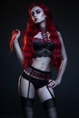Beautiful gothic woman in lingerie posing at camera on black background