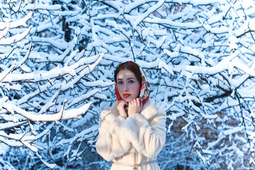 Beautiful European fashionable woman at winter, in a headscarf on her head, against the background of trees. Fairy-tale winter, Vintage red lips and bright eyes. Snow falls