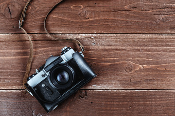 Retro photo camera is lying on a wooden background with a lot of free space on it