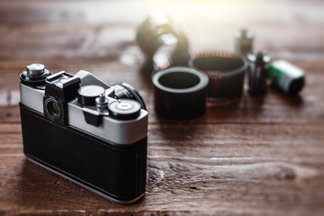 Retro photo camera on a stylish wooden background with different photo related items