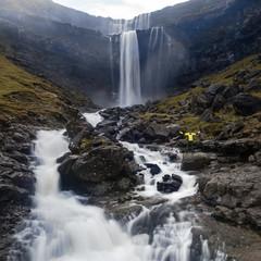 Beautiful waterfall falls down from the rocky cliff on Faroe Isl
