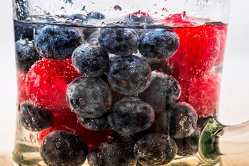 Heap of blueberries and raspberries in dewy glass with drink.